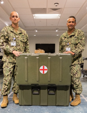 two male military personnel opening a large medical kitting unit