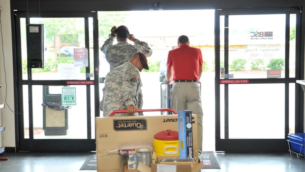 military personnel leaving an LCI base supply center with the gear and materials they've purchased